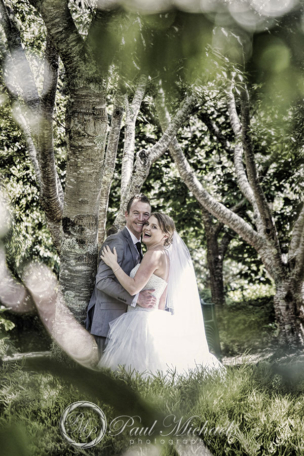 Bride and groom through the trees